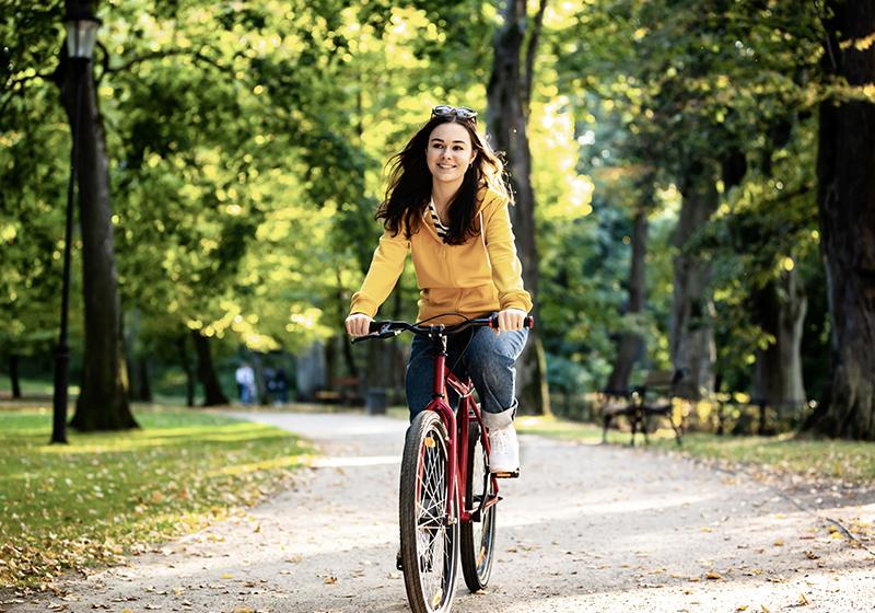 En kvinna cyklar i en park
