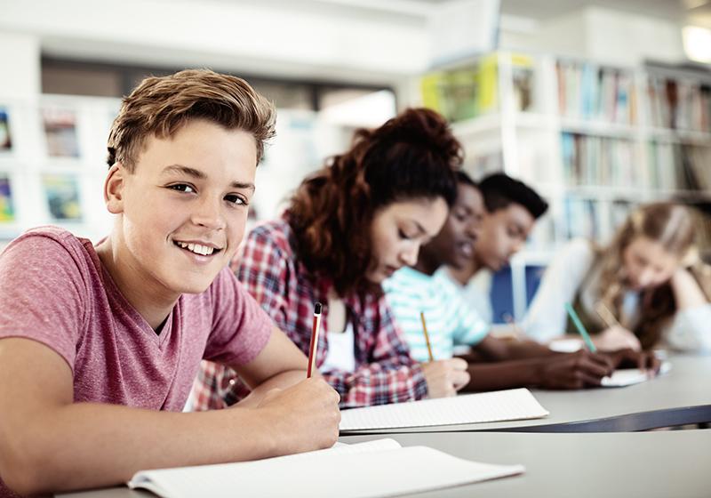 Elev sitter i klassrummet tillsammans med sin klasskompisar. Skriver på ett papper och tittar in i kameran samtidigt.