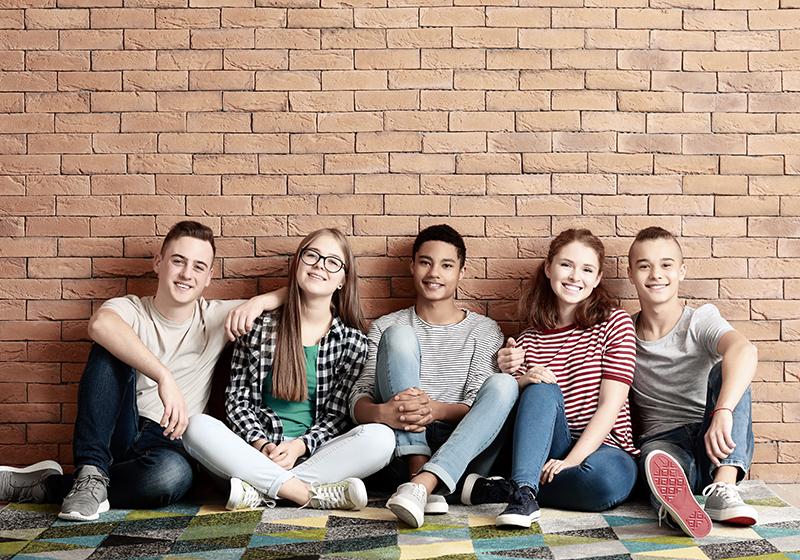 Gruppbild på tonåringar framför tegelvägg