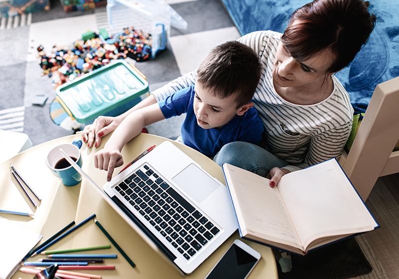 Mamma och son sitter vid ett bord framför en laptop