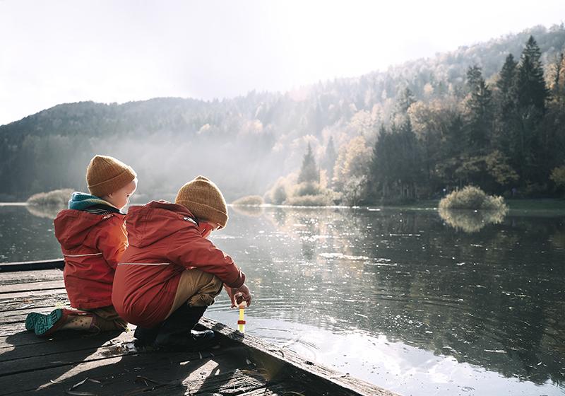 två barn sitter på bryggan vid en sjö