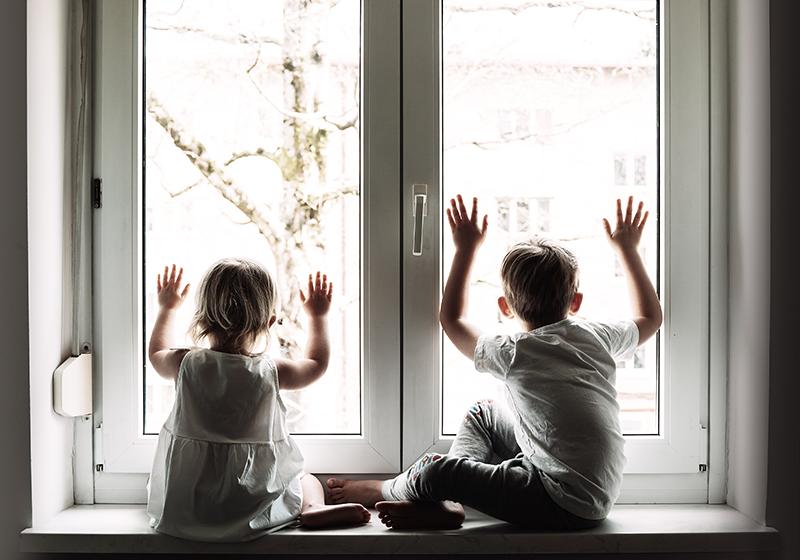 Två barn sitter i ett fönster och tittar ut.