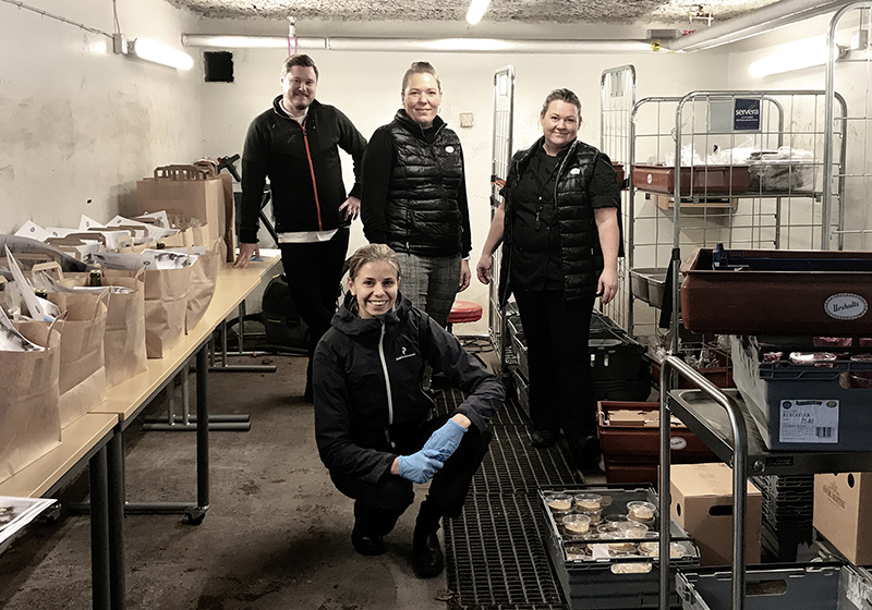 En bild på fyra medarbetare i ett garage fyllt med kassar med mat