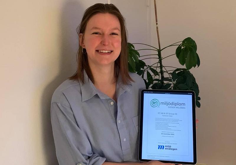 Vår Sustainability Manager Elisabeth Wandel håller upp vårt miljöcertifikat från Svensk Miljöbas
