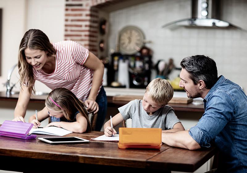 En familj med en mamma, en pappa, en dotter och en son sitter vid middagsbordet och gör läxor