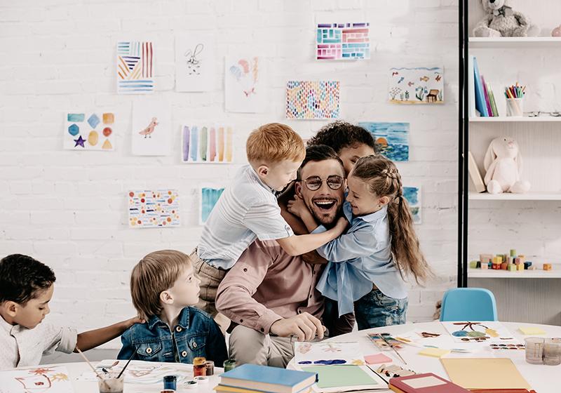 En lärare i ett klassrum blir kramad av två barn