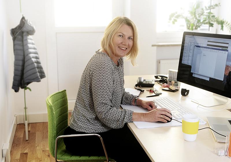En kvinna sitter i ett soligt rum framför en dator, tittar in i kameran och ler
