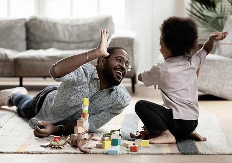 En pappa och ett barn leker med leksaker på golvet och ger varandra en high five