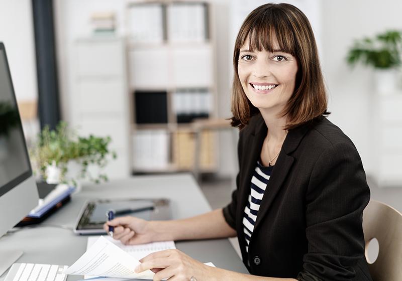 En kvinna sitter vid ett skrivbord framför en dator, tittar in i kameran och ler