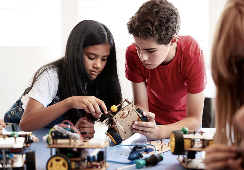 En tjej och en kille lutar sig över ett bord där de bygger en robot tillsammans