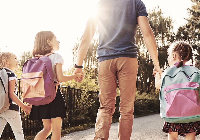 Förälder som följer sina tre barn till skolan en solig morgon.