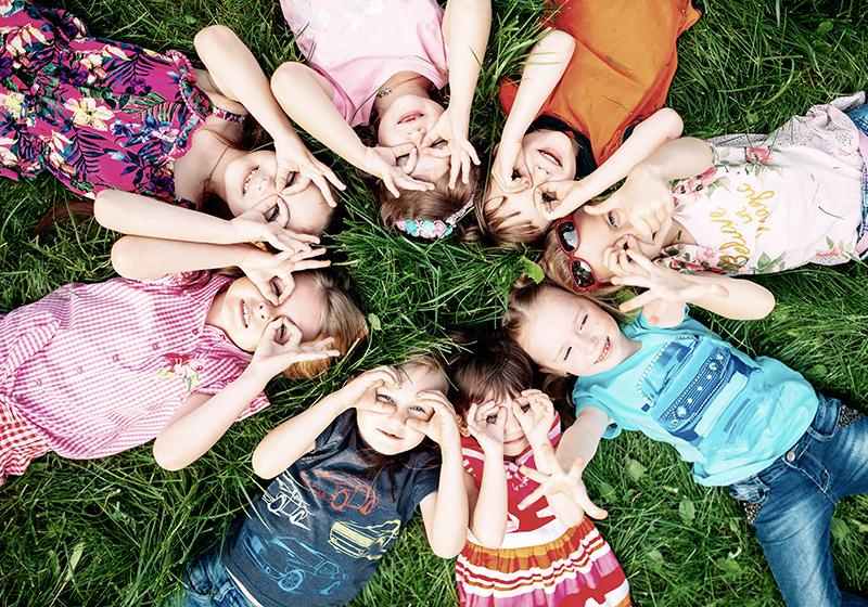 Barn som ligger i en ring i gräset och kisar upp mot himlen.