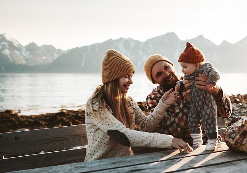 En familj med en mamma, en pappa och ett barn sitter vid ett bord utomhus. I bakgrunden syns en sjö och berg.