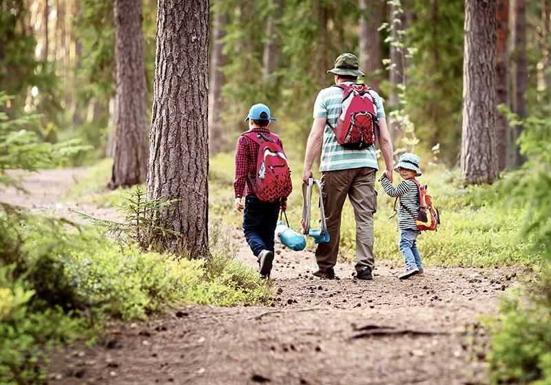 En familj med en förälder och två barn går på en stig i skogen.