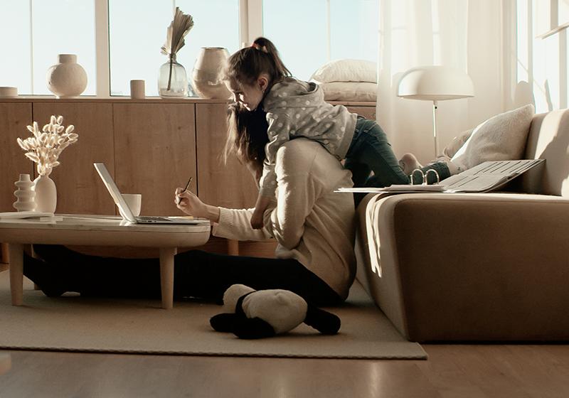 En förälder sitter på golvet framför en laptop. Ett barn sträcker sig från soffan över till föräldern.