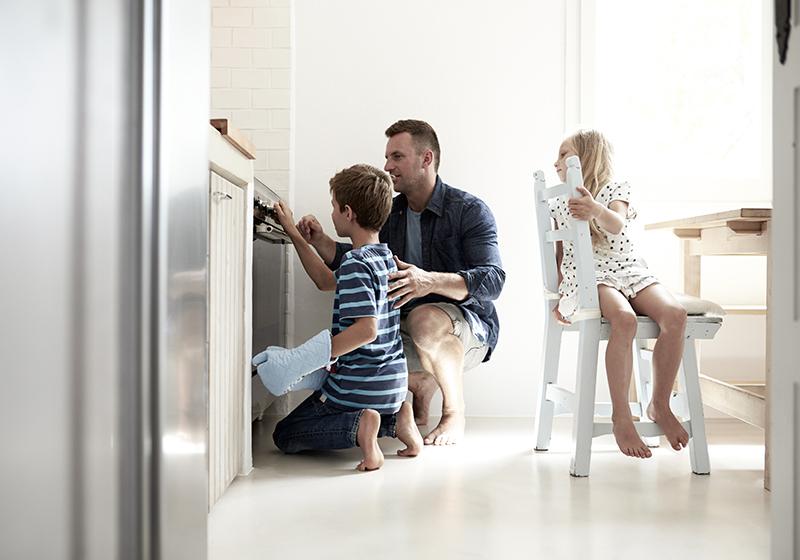 En pappa sitter framför en ugn med sina två barn