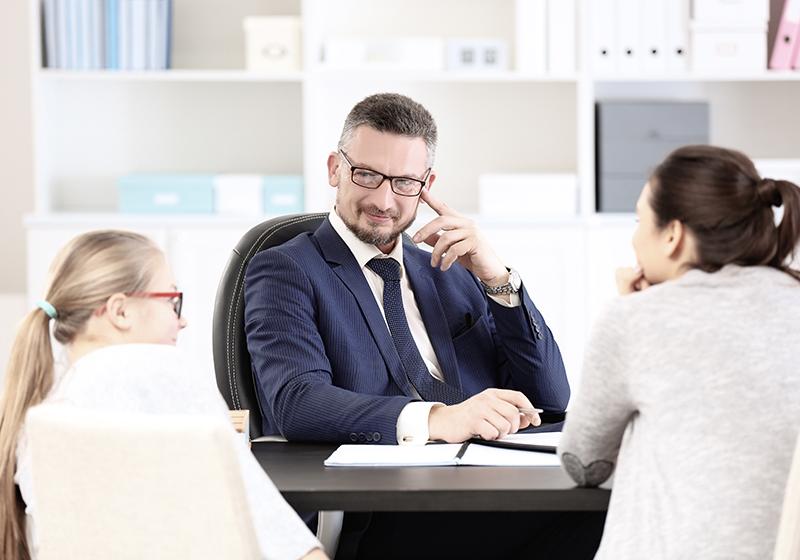 En mamma och en dotter sitter mittemot en manlig lärare vid ett skrivbord.