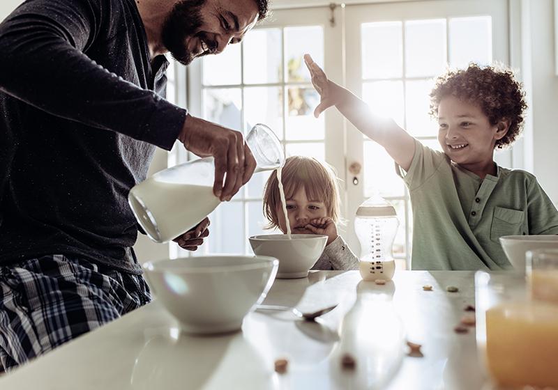 En pappa gör frukost till sina två barn