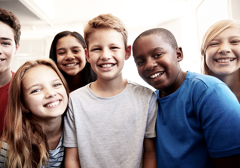 En grupp elever ler för kameran