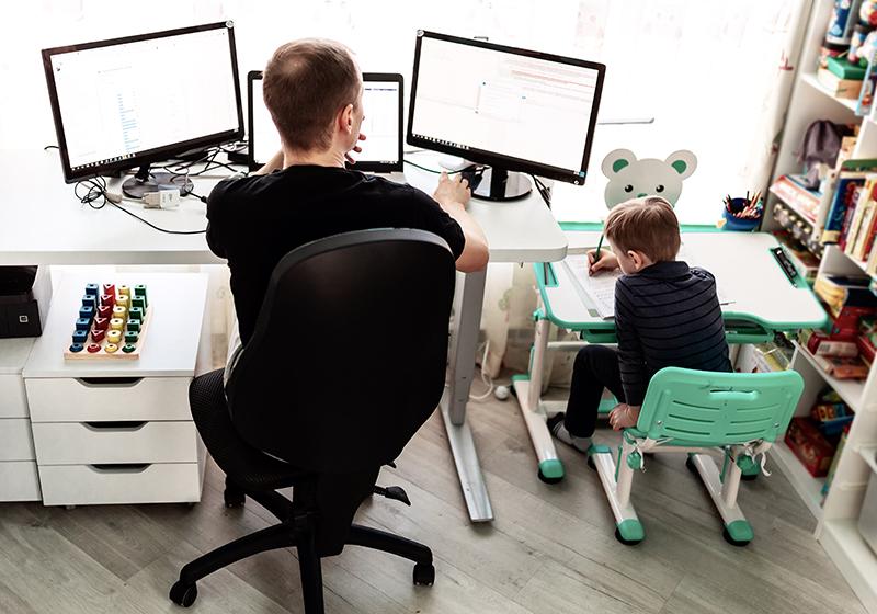 En pappa och ett barn sitter bredvid varandra vid ett skrivbord. Båda har varsin datorskärm framför sig.