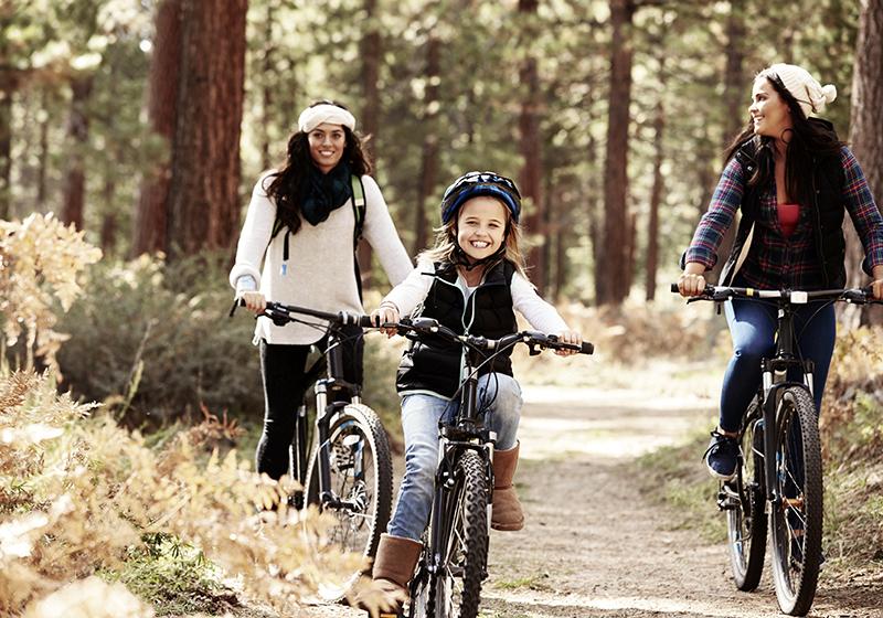 Res tillsammans - appen som förenklar samåkning mellan familjer. På bilder cyklar två vuxna och ett barn tillsammans på en skogsväg.