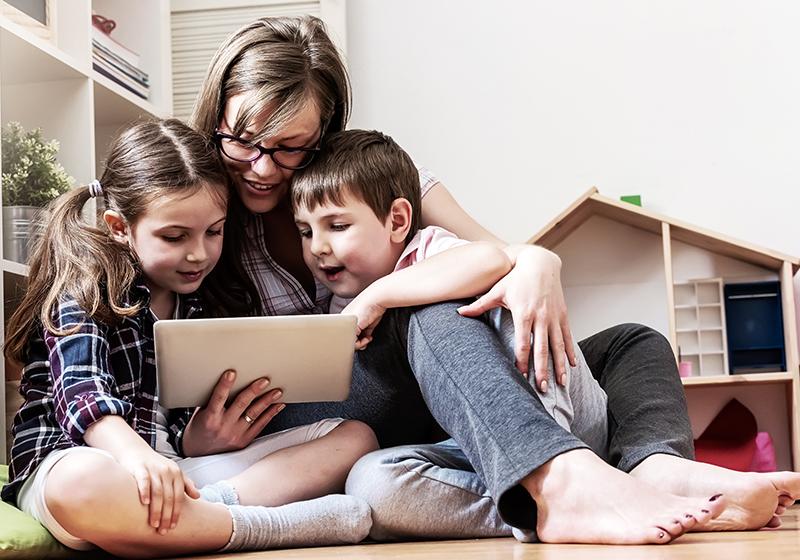 En mamma och två barn sitter på golvet framför en ipad