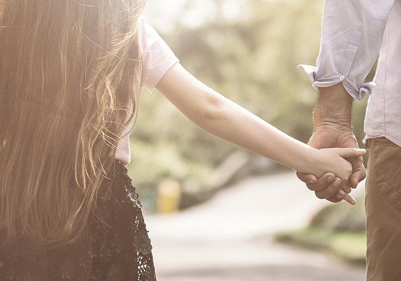 Barn som håller vuxen i handen