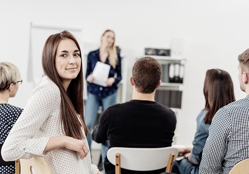 En kvinna sitter och tittar över axeln in i kameran. I bakgrunden syns ett klassrum och en lärare.
