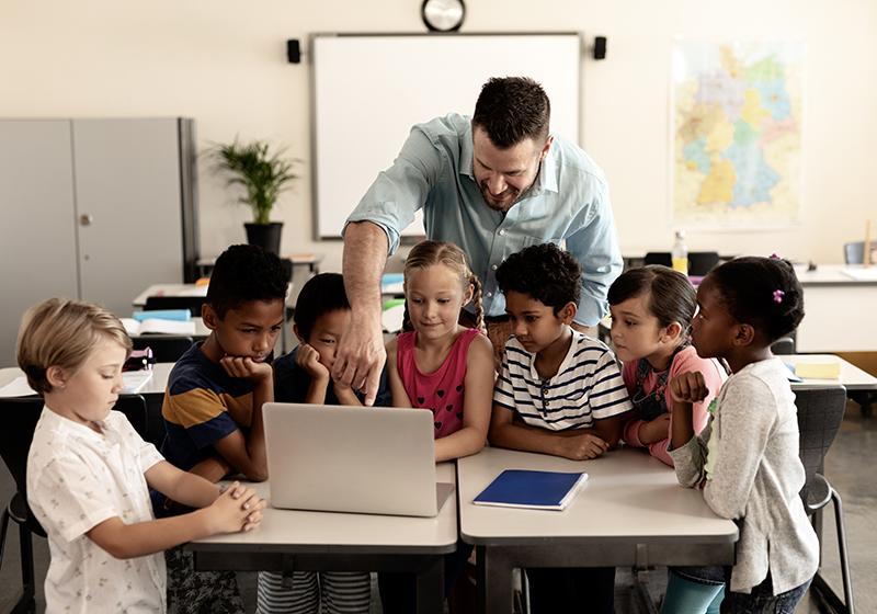 En manlig lärare står bakom en grupp barn som tittar på en datorskärm.