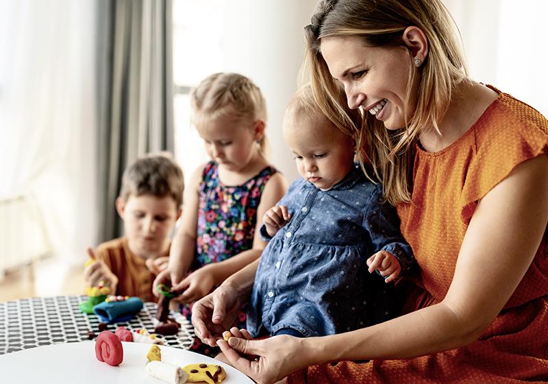 En kvinna sitter med ett barn i knät och brevid två barn och leker vid ett bord.