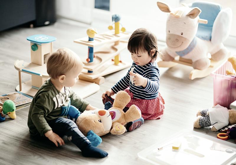 Två barn sitter på ett golv och leker med klossar.