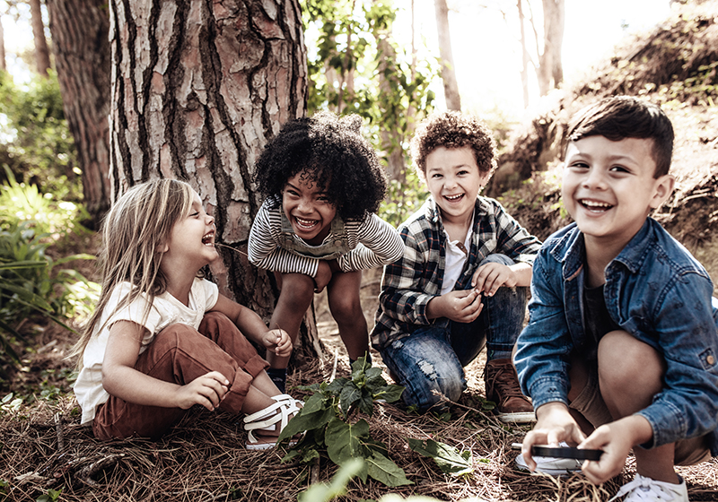 Children sitting in the forest, smiling to the camera